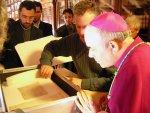Il Vescovo osserva con iteresse le antiche pergamene, lustro dell'archivio storico parrocchiale